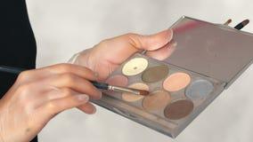 O artista de composição usa uma paleta das sombras para os olhos em um salão de beleza video estoque