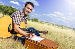 O artista de viagem escreve uma canção na natureza Fotografia de Stock Royalty Free