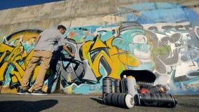 O artista dos grafittis está vindo até a parede e começando pintar o cinza, backpack no primeiro plano filme