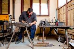 O artista está fazendo a figura soldando poucos fios de metal em seu worksh foto de stock