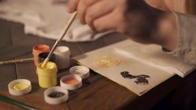 O artista está misturando o amarelo e o branco tinge-se em uma paleta antes de tirar, close-up video estoque