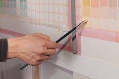 O artista está pintando uma imagem - quadrados usando uma escova de pintura Imagem de Stock
