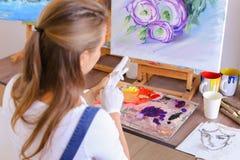 O artista expulsa pintura dos tubos na paleta para as cores de mistura t foto de stock