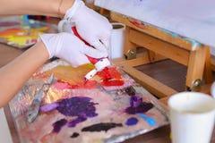 O artista expulsa pintura dos tubos na paleta para as cores de mistura t fotografia de stock royalty free
