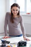O artista fêmea atrativo da foto está trabalhando no escritório fotos de stock