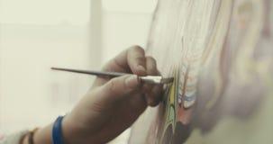 O artista fêmea bonito novo está em Art Studio, sentando-se atrás de uma armação e pintando na lona Processo de tiragem: em video estoque