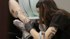 O artista fêmea da tatuagem faz a arte da tatuagem disponível de seu cliente masculino vídeos de arquivo