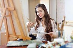 O artista fêmea de cabelos compridos pinta a imagem na lona fotografia de stock