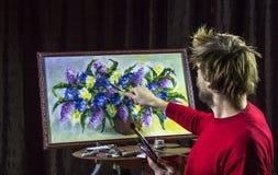 O artista farpado masculino em uma camiseta vermelha tira com vida das flores da pintura da faca de paleta ainda no estúdio Fotos de Stock Royalty Free
