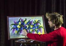 O artista farpado masculino em uma camiseta vermelha tira uma vida artística das flores da pintura da escova ainda no estúdio Fotografia de Stock Royalty Free