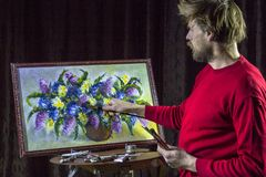 O artista farpado masculino em uma camiseta vermelha tira uma vida artística das flores da pintura da escova ainda no estúdio Fotos de Stock