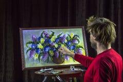 O artista farpado masculino em uma camiseta vermelha tira uma vida artística das flores da pintura da escova ainda no estúdio Fotografia de Stock