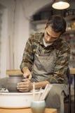 O artista faz a cerâmica da argila em uma roda da rotação foto de stock royalty free