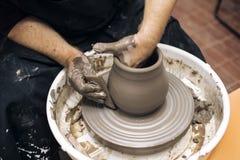 O artista faz a cerâmica da argila em uma roda da rotação imagem de stock