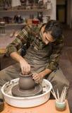 O artista faz a cerâmica da argila em uma roda da rotação fotos de stock