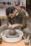 O artista faz a cerâmica da argila em uma rotação rodar dentro a oficina fotos de stock