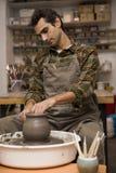 O artista faz a cerâmica da argila em uma rotação rodar dentro a oficina fotografia de stock