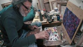 O artista grisalho mistura pinturas de óleo para pintar 4K filme