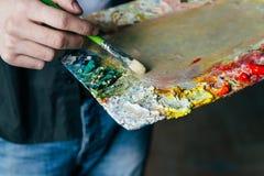O artista guarda uma paleta com pinturas e uma escova e está indo pintar na lona para misturar pinturas de óleo imagens de stock