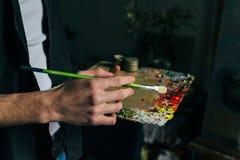 O artista guarda uma paleta com pinturas e uma escova e está indo pintar na lona para misturar pinturas de óleo foto de stock royalty free