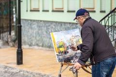 O artista idoso pinta uma imagem do óleo na descida de Andrew Fotos de Stock Royalty Free