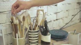 O artista masculino está tomando a escova para pintar na oficina da cerâmica filme