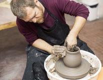 O artista masculino faz a cerâmica da argila em uma roda da rotação imagem de stock royalty free