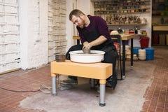 O artista masculino faz a cerâmica da argila em uma roda da rotação imagens de stock