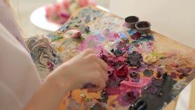O artista mistura pinturas de óleo em uma paleta com uma escova, close-up filme