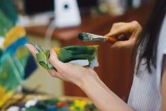 O artista mistura pinturas de óleo na pálete com o vário Fotografia de Stock Royalty Free