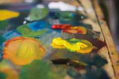 O artista mistura pinturas de óleo na pálete com o vário Imagens de Stock