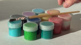 O artista põe a escova sobre os frascos da pintura acrílica do guache vídeos de arquivo