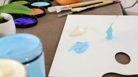 O artista põe uma espátula azul da pintura sobre a paleta para misturar cores filme