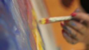O artista pinta uma pintura a óleo em um estúdio, pintor no trabalho, criador faz a obra de arte, as escovas e as pinturas vídeos de arquivo