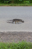 O asfalto foi danificado e caldeirões perigosos. fotografia de stock