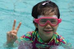 O asiático do estilo de vida da juventude dos óculos de proteção do sorriso da nadada da menina aprecia o roupa de banho Foto de Stock