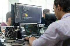 O asiático externaliza o colaborador que olha a tela que senta-se no funcionamento da mesa fotografia de stock