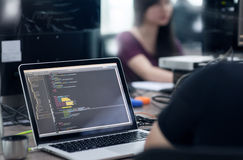O asiático externaliza o portátil de Team Sitting At Desk Working do colaborador foto de stock
