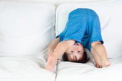 O asiático, menino da criança da raça misturada que tenta um suporte da mão e é de cabeça para baixo. Foto de Stock Royalty Free