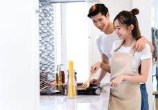O asiático novo dos pares equipa junto e mulher que cozinha o alimento para a salada do jantar foto de stock