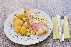 O aspargo branco fervido com o presunto e as batatas fervidas novas frescas serviu com o molho do hollandaise Fotografia de Stock