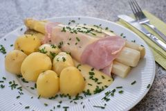 O aspargo branco fervido com o presunto e as batatas fervidas novas frescas serviu com o molho do hollandaise Imagens de Stock
