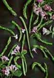 O aspargo verde, aspargo derruba bonito arranjado na madeira escura com flores cor-de-rosa Fotos de Stock Royalty Free