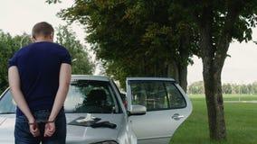 O assaltante detido nas algemas está perto de um carro roubado vídeos de arquivo