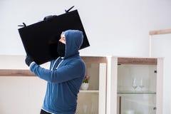 O assaltante do homem que rouba o aparelho de televisão da casa imagem de stock