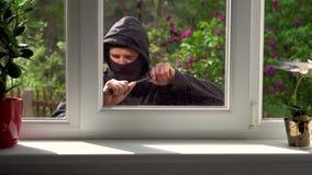 O assaltante quebra em uma casa através da janela