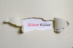 O assassino silencioso da palavra que aparece atrás do papel rasgado Foto de Stock