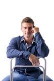 O assento atrativo do homem novo, inclinando-se sobre suporta da imagens de stock royalty free