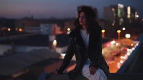 O assento da mulher em olhares do terracce aprecia ao redor a calma da cidade da noite vídeos de arquivo