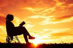 O assento das mulheres da silhueta leu um livro no feriado foto de stock